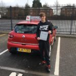Image of Oliver Griffiths displaying his test pass certificate next to Saras' car.