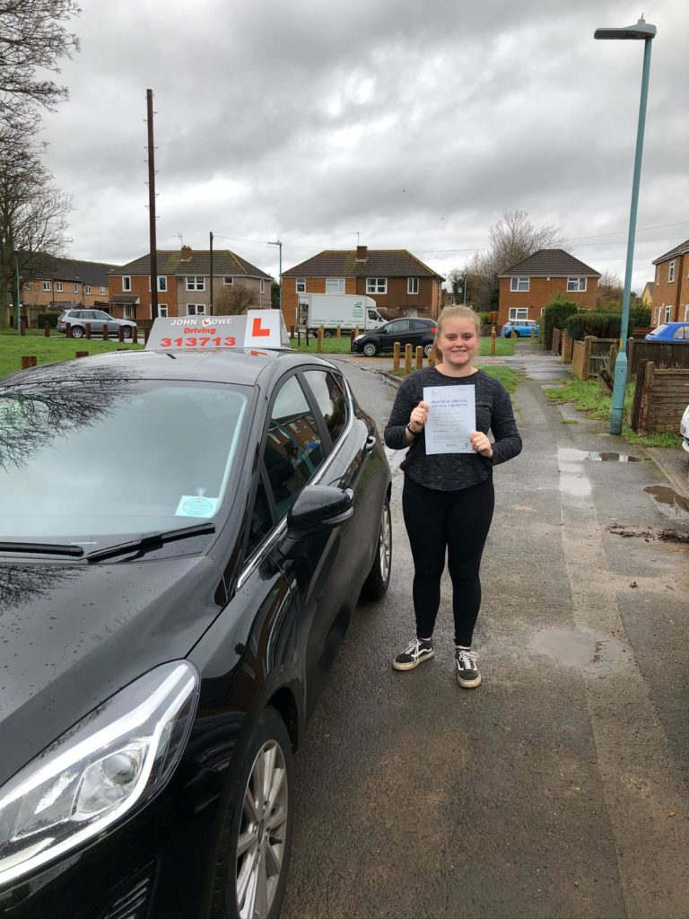Image of Courtney next to Toms car, showing her test pass certificate.