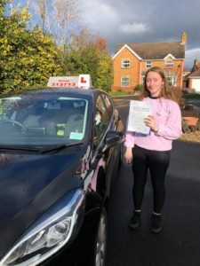 Image of Lucy Dingle after her driving test pass. She is next to Toms car, showing her certificate.