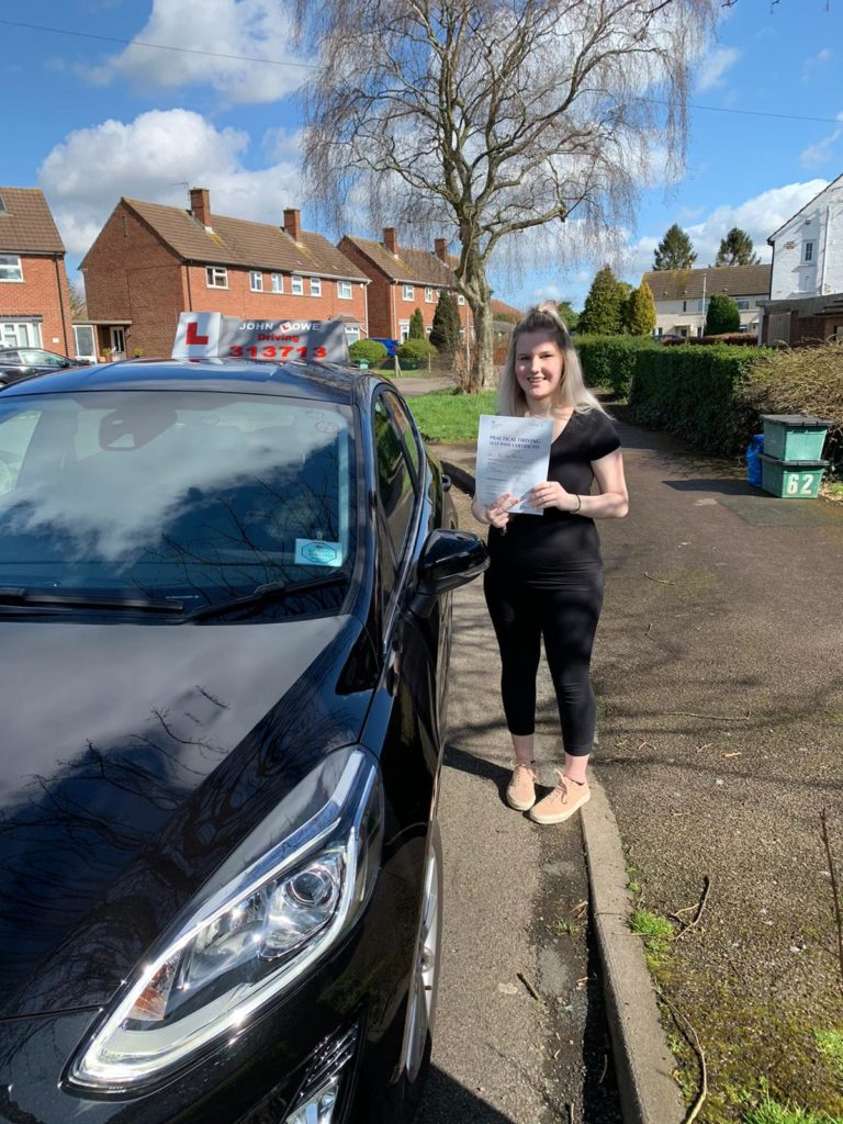 Picture Of Chloe Martin showing her test pass certificate, in front of Toms car.